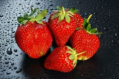 在一黑暗的背景wate的五个大成熟红色草莓莓果 免版税库存照片