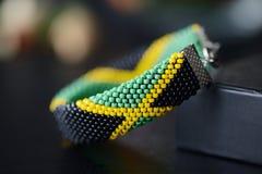 在一黑暗的bakground的牙买加旗子小珠钩针编织镯子 库存照片