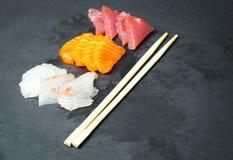 在一黑石slatter的新鲜的生鱼片 三文鱼,金枪鱼大虾和酱油 烹调日本传统 库存图片