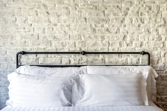 在一间经典卧室的白色枕头有白色砖墙的 库存图片