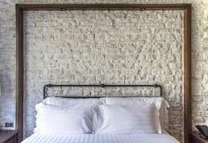 在一间经典卧室的白色枕头有白色砖墙的 免版税库存照片