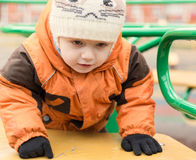 在一件夹克和一个温暖的盖帽的孩子,在一个操场在秋天da 免版税库存照片