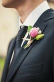 在一件黑夹克的钮扣眼上插的花 图库摄影