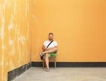 在一间破旧的屋子供以人员坐一把木椅子用桔子 免版税库存图片