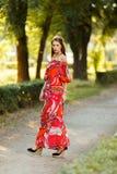 在一件明亮的礼服的美好的模型在街道上 免版税库存照片