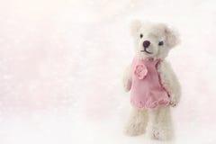 在一件桃红色毛线衣的玩具熊在轻的背景 库存图片