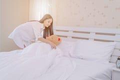 在一头熊包裹的美丽的女孩在床上 免版税库存图片