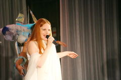 在一件白色礼服的音乐会阶段,带薄菏的榜样歌手,侈奢的歌唱者安娜Malysheva 红色 免版税库存照片