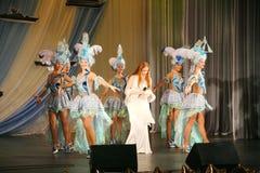 在一件白色礼服的音乐会阶段,带薄菏的榜样歌手,侈奢的歌唱者安娜Malysheva 红色 库存图片