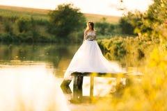 在一件礼服的画象在湖附近的日落 免版税库存图片