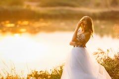 在一件礼服的画象在湖附近的日落 库存照片