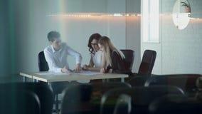 在一间空的会议室,三名雇员为纸超时工作 股票视频