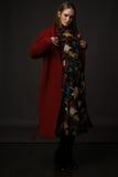 在一件红色外套的时髦的女孩模型在灰色背景 库存照片
