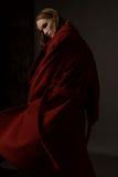 在一件红色外套的时髦的女孩模型在灰色背景 免版税库存图片