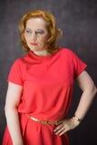 在一件红色礼服打扮的红发妇女 免版税图库摄影