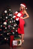 在一件红色礼服的性感的白肤金发的圣诞老人有在圣诞树附近的礼物的 库存照片