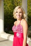 去在一件红色礼服的正式舞会的愉快的十几岁的女孩 免版税库存图片