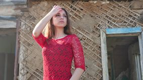 在一件红色礼服的美好的女孩生活方式 礼服的性感的女孩在废墟的老房子旁边站立 免版税图库摄影