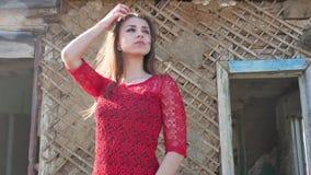 在一件红色礼服的美好的女孩生活方式 礼服的性感的女孩在废墟的老房子旁边站立 免版税库存图片