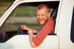 在一件红色衬衣的司机,当驾驶时 免版税库存图片