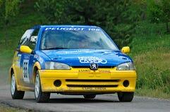 在一黄色和蓝色葡萄酒标致汽车106的未认出的司机赛车 免版税库存照片