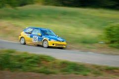 在一黄色和蓝色葡萄酒标致汽车106的未认出的司机赛车 免版税图库摄影
