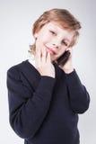 在一件蓝色毛线衣的年轻商人谈话在电话和smi 免版税库存照片