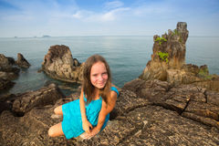 在一件蓝色礼服的Teengirl在海岸岩石  免版税图库摄影