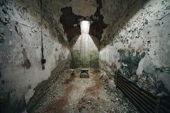 在一间被放弃的监狱牢房的微小的凳子 库存图片