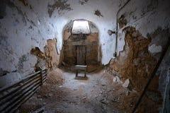 在一间被放弃的监狱牢房的微小的凳子 图库摄影