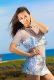 在一件银色礼服的美好的亚洲模型 免版税库存照片
