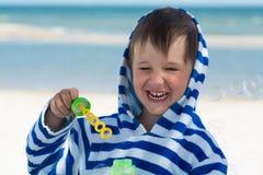 在一件镶边长袍的一个小逗人喜爱的孩子吹泡影以海和一条被洗涤的辫子为背景 婴孩得到了肥皂泡 库存照片