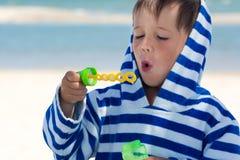 在一件镶边长袍的一个小逗人喜爱的孩子吹肥皂泡以海和被洗涤的辫子为背景 婴孩得到空气 免版税库存图片