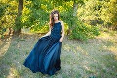 在一件长的蓝色礼服的深色的跳舞 免版税库存照片