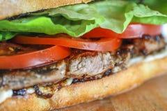 在一ciabatta用蕃茄,莴苣的鲜美猪肉牛排三明治 免版税图库摄影