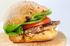 在一ciabatta用蕃茄,莴苣的鲜美猪肉牛排三明治 免版税库存图片
