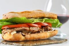 在一ciabatta用蕃茄,莴苣的鲜美猪肉牛排三明治 免版税库存照片
