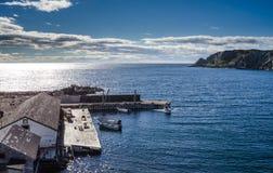在一cliffside dockhouse的小船在Twillingate,纽芬兰 免版税库存图片