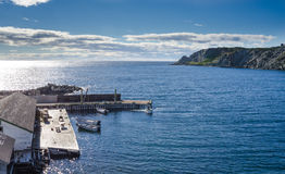 在一cliffside dockhouse的小船在Twillingate,纽芬兰 库存照片