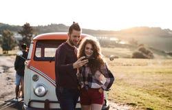 在一roadtrip的一对年轻夫妇通过乡下,使用在智能手机的地图 免版税库存图片