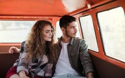 在一roadtrip的一对年轻夫妇通过乡下,坐在微型货车 库存照片