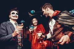 在万圣夜党的青年人饮用的鸡尾酒 免版税库存照片