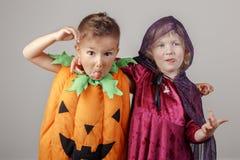 在万圣夜打扮的两个白白种人可爱的孩子 免版税图库摄影