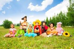 在万圣夜服装的愉快的孩子坐草 免版税库存照片