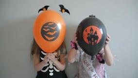 在万圣节服装打扮的结合两微笑的女孩举行气球和摆在 股票录像