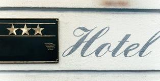 在三个星门面旁边的美好的旅馆书法标志 免版税库存图片