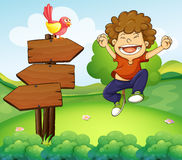 在三个木箭头旁边的一个愉快的年轻男孩 库存照片