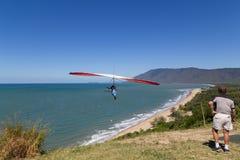 在三位一体海湾监视,昆士兰,澳大利亚的悬挂式滑翔机 图库摄影