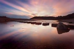 在三峭壁海湾的日落 库存图片