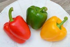 在三种颜色的胡椒在一块白色自然板材 免版税库存照片